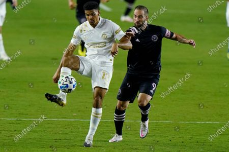 Atlanta United defender Miles Robinson (12) controls the ball as Inter Miami attacker Gonzalo Higuain closes in during the first half of an MLS soccer match, in Fort Lauderdale, Fla
