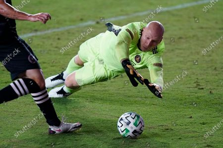 Atlanta United goalkeeper Brad Guzan dives on a shot by Inter Miami attacker Gonzalo Higuain during the first half of an MLS soccer match, in Fort Lauderdale, Fla