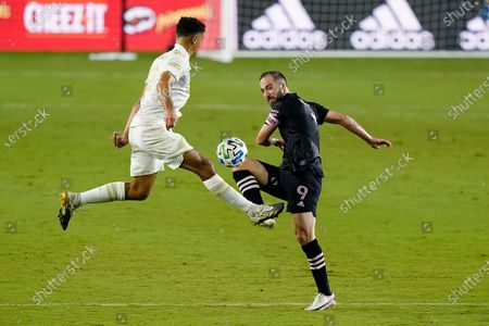 Inter Miami attacker Gonzalo Higuain (9) passes past Atlanta United defender Miles Robinson during the first half of an MLS soccer match, in Fort Lauderdale, Fla