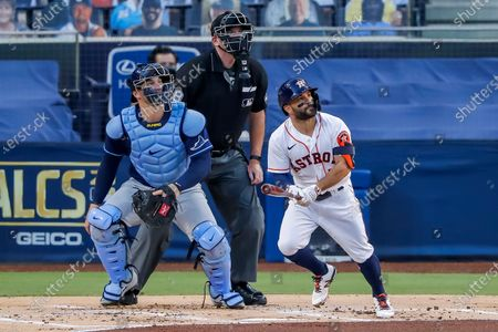 Houston Astros second baseman Jose Altuve (R) hits a solo home run as umpire Chris Conroy (C) and Tampa Bay Rays catcher Mike Zunino (L) look on in the first inning of the American League Championship Series playoff game four between the Tampa Bay Rays and the Houston Astros at Petco Park in San Diego, California, USA, 14 October 2020.
