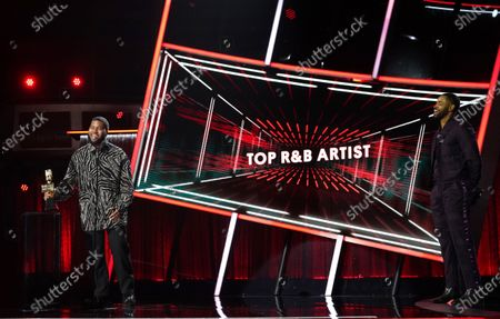 Khalid accepts his award for Top R&B Artist as presenter Jay Ellis looks on during the 2020 Billboard Music Awards held at the Dolby Theatre in Hollywood, CA. (Andrew Gombert / Los Angeles Times)
