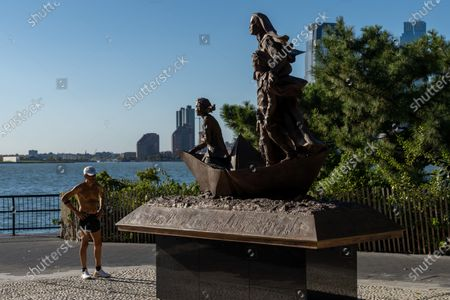 "Stock Picture of A jogger stands in front of the statue of Mother Cabrini in Battery Park City, New York City. A year after a tribute to Mother Cabrini was skipped by City Hall's much vaunted ""She Built NYC"" commission, Governor Andrew Cuomo gave America's first saint the respect she deserved with the unveiling of the new statue in Battery Park City for Columbus Day. Normally, Cuomo would be leading the Columbus Day Parade up Fifth Avenue, but COVID-19 resulted in the cancellation of most every major parade in the city. The governor told members of the Columbus Citizens Foundation that he would unveil the statue to mark the Columbus Day celebration."
