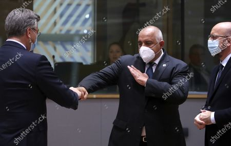 Bulgaria's Prime Minister Boyko Borissov, center, greets Croatia's Prime Minister Andrej Plenkovic, left, with a fist bump during a round table meeting at an EU summit at the European Council building in Brussels, . European Union leaders are meeting in person for a two-day summit amid the worsening coronavirus pandemic to discuss topics ranging from Brexit to climate and relations with Africa