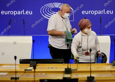 Members of the cleaning crew sanitize a room prior to a media conference of Sinn Fein's President Mary Lou McDonald at the European Parliament in Brussels