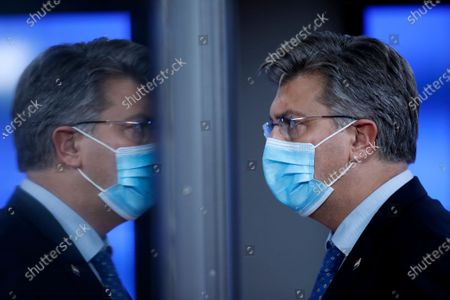 Croatia's Prime Minister Andrej Plenkovic is reflected in a glass door as he leaves during departures at an EU summit in Brussels, . European Union leaders met in person for the first day of a two-day summit, amid the worsening coronavirus pandemic, to discuss topics ranging from Brexit to climate and relations with Africa