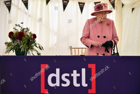 Queen Elizabeth II stands after signing a visitor's book during her visit to the Defence Science and Technology Laboratory (Dstl) at Porton Down science park near Salisbury, southern England, on October 15, 2020.