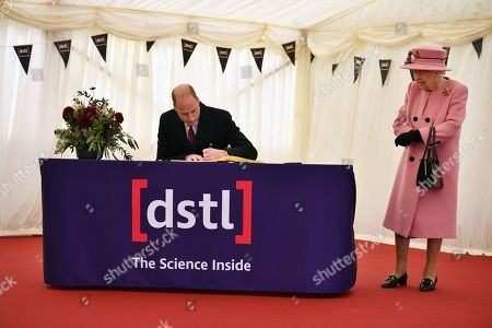 Queen Elizabeth II (R) stands by as Prince William (L) signs a visitor's book during their visit to the Defence Science and Technology Laboratory (Dstl) at Porton Down science park near Salisbury, southern England, on October 15, 2020.