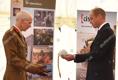 Britain's Prince William, Prince William, (R) presents British Army Colonel Mike Duff (L), Assistant Commander South West and deputy joint commander for the decontamination of Salisbury following the 2018 Novichok incident, with the Firmin Sword of Peace for the South West department's work on the Novichok incident, during the Duke's visit to the Defence Science and Technology Laboratory (Dstl) at Porton Down science park near Salisbury, southern England
