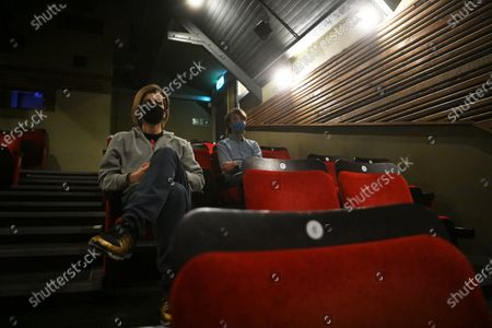 People wear face masks as they sit ahead of a screening at the independent Arthouse cinema in Crouch End in north London, Britain, 15 October 2020. Due to coronavirus restrictions, the Cineworld and Picturehouse cinema chains have closed indefinitely whilst Vue cinemas have cut back screenings. Major films such as the latest James Bond and Death on the Nile have been rescheduled, and Disney showed its latest release Mulan on its streaming service, which has caused concern for the cinema industry trying to bounce back with Covid-19 restrictions. Roisin McNeill is the manager at the independent Arthouse cinema in Crouch End in north London. She says, 'We have cut down our seating from 80 to 40. We thought that business might be quiet, but actually, on weekends, we are sold out. Customers can find it tricky to follow the face mask rules, but we try to make sure everyone is as safe as possible. Blockbusters such as James Bond being pulled from the release is a real problem for multiplexes and big cinema chains. They rely on these big films for business. As a small independent cinema, we have built a loyal customer following and are able to be successful with independent cinema. Hopefully, this means we can weather the storm although there is always the worry about time if there are no films to show. We have a good relationship with the National Theatre playing performances of plays, which there is a big audience for. With streaming services, there is a view that they are the villain taking content away from cinemas - but we show things that go to Netflix or Amazon after a few weeks, and they are popular. Parasite, the Irishman, and Fleabag all went to streaming services but were good business for the cinema. I don't foresee a time when people don't want to go to the cinema. We get people thinking we won't survive Covid, but we keep positive. There is not much positivity for people, but cinema does the world of good for them. It is great to take people out of the daily l