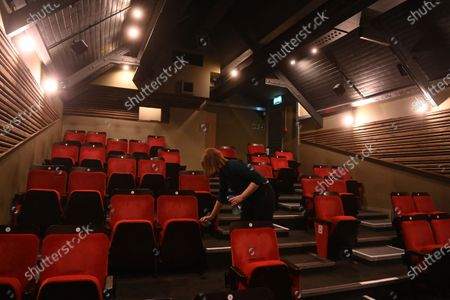 Cinema manager Roisin McNeill cleans seating at the independent Arthouse cinema in Crouch End in north London, Britain, 15 October 2020. Due to coronavirus restrictions, the Cineworld and Picturehouse cinema chains have closed indefinitely whilst Vue cinemas have cut back screenings. Major films such as the latest James Bond and Death on the Nile have been rescheduled, and Disney showed its latest release Mulan on its streaming service, which has caused concern for the cinema industry trying to bounce back with Covid-19 restrictions. Roisin McNeill is the manager at the independent Arthouse cinema in Crouch End in north London. She says, 'We have cut down our seating from 80 to 40. We thought that business might be quiet, but actually, on weekends, we are sold out. Customers can find it tricky to follow the face mask rules, but we try to make sure everyone is as safe as possible. Blockbusters such as James Bond being pulled from the release is a real problem for multiplexes and big cinema chains. They rely on these big films for business. As a small independent cinema, we have built a loyal customer following and are able to be successful with independent cinema. Hopefully, this means we can weather the storm although there is always the worry about time if there are no films to show. We have a good relationship with the National Theatre playing performances of plays, which there is a big audience for. With streaming services, there is a view that they are the villain taking content away from cinemas - but we show things that go to Netflix or Amazon after a few weeks, and they are popular. Parasite, the Irishman, and Fleabag all went to streaming services but were good business for the cinema. I don't foresee a time when people don't want to go to the cinema. We get people thinking we won't survive Covid, but we keep positive. There is not much positivity for people, but cinema does the world of good for them. It is great to take people out of the daily life particu
