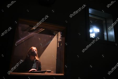 Cinema manager Roisin McNeill wears a face mask as she prepares the program in the projectionist booth at the independent Arthouse cinema in Crouch End in north London, Britain, 15 October 2020. Due to coronavirus restrictions, the Cineworld and Picturehouse cinema chains have closed indefinitely whilst Vue cinemas have cut back screenings. Major films such as the latest James Bond and Death on the Nile have been rescheduled, and Disney showed its latest release Mulan on its streaming service, which has caused concern for the cinema industry trying to bounce back with Covid-19 restrictions. Roisin McNeill is the manager at the independent Arthouse cinema in Crouch End in north London. She says, 'We have cut down our seating from 80 to 40. We thought that business might be quiet, but actually, on weekends, we are sold out. Customers can find it tricky to follow the face mask rules, but we try to make sure everyone is as safe as possible. Blockbusters such as James Bond being pulled from the release is a real problem for multiplexes and big cinema chains. They rely on these big films for business. As a small independent cinema, we have built a loyal customer following and are able to be successful with independent cinema. Hopefully, this means we can weather the storm although there is always the worry about time if there are no films to show. We have a good relationship with the National Theatre playing performances of plays, which there is a big audience for. With streaming services, there is a view that they are the villain taking content away from cinemas - but we show things that go to Netflix or Amazon after a few weeks, and they are popular. Parasite, the Irishman, and Fleabag all went to streaming services but were good business for the cinema. I don't foresee a time when people don't want to go to the cinema. We get people thinking we won't survive Covid, but we keep positive. There is not much positivity for people, but cinema does the world of good for them