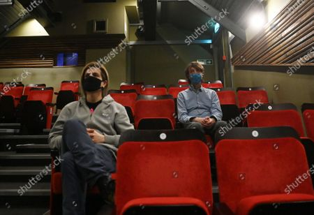 People wear face mask as they sit ahead of a screening at the independent Arthouse cinema in Crouch End in north London, Britain, 15 October 2020. Due to coronavirus restrictions, the Cineworld and Picturehouse cinema chains have closed indefinitely whilst Vue cinemas have cut back screenings. Major films such as the latest James Bond and Death on the Nile have been rescheduled, and Disney showed its latest release Mulan on its streaming service, which has caused concern for the cinema industry trying to bounce back with Covid-19 restrictions. Roisin McNeill is the manager at the independent Arthouse cinema in Crouch End in north London. She says, 'We have cut down our seating from 80 to 40. We thought that business might be quiet, but actually, on weekends, we are sold out. Customers can find it tricky to follow the face mask rules, but we try to make sure everyone is as safe as possible. Blockbusters such as James Bond being pulled from the release is a real problem for multiplexes and big cinema chains. They rely on these big films for business. As a small independent cinema, we have built a loyal customer following and are able to be successful with independent cinema. Hopefully, this means we can weather the storm although there is always the worry about time if there are no films to show. We have a good relationship with the National Theatre playing performances of plays, which there is a big audience for. With streaming services, there is a view that they are the villain taking content away from cinemas - but we show things that go to Netflix or Amazon after a few weeks, and they are popular. Parasite, the Irishman, and Fleabag all went to streaming services but were good business for the cinema. I don't foresee a time when people don't want to go to the cinema. We get people thinking we won't survive Covid, but we keep positive. There is not much positivity for people, but cinema does the world of good for them. It is great to take people out of the daily li