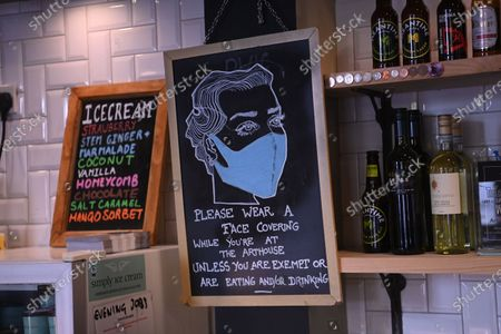 A sign encouraging face masks to be worn is displayed at the independent Arthouse cinema in Crouch End in north London, Britain, 15 October 2020. Due to coronavirus restrictions, the Cineworld and Picturehouse cinema chains have closed indefinitely whilst Vue cinemas have cut back screenings. Major films such as the latest James Bond and Death on the Nile have been rescheduled, and Disney showed its latest release Mulan on its streaming service, which has caused concern for the cinema industry trying to bounce back with Covid-19 restrictions. Roisin McNeill is the manager at the independent Arthouse cinema in Crouch End in north London. She says, 'We have cut down our seating from 80 to 40. We thought that business might be quiet, but actually, on weekends, we are sold out. Customers can find it tricky to follow the face mask rules, but we try to make sure everyone is as safe as possible. Blockbusters such as James Bond being pulled from the release is a real problem for multiplexes and big cinema chains. They rely on these big films for business. As a small independent cinema, we have built a loyal customer following and are able to be successful with independent cinema. Hopefully, this means we can weather the storm although there is always the worry about time if there are no films to show. We have a good relationship with the National Theatre playing performances of plays, which there is a big audience for. With streaming services, there is a view that they are the villain taking content away from cinemas - but we show things that go to Netflix or Amazon after a few weeks, and they are popular. Parasite, the Irishman, and Fleabag all went to streaming services but were good business for the cinema. I don't foresee a time when people don't want to go to the cinema. We get people thinking we won't survive Covid, but we keep positive. There is not much positivity for people, but cinema does the world of good for them. It is great to take people out of the daily lif