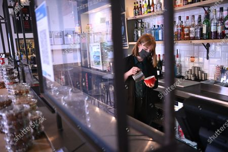 Cinema manager Roisin McNeill prepares a drink behind a protective screen at the independent Arthouse cinema in Crouch End in north London, Britain, 15 October 2020. Due to coronavirus restrictions, the Cineworld and Picturehouse cinema chains have closed indefinitely whilst Vue cinemas have cut back screenings. Major films such as the latest James Bond and Death on the Nile have been rescheduled, and Disney showed its latest release Mulan on its streaming service, which has caused concern for the cinema industry trying to bounce back with Covid-19 restrictions. Roisin McNeill is the manager at the independent Arthouse cinema in Crouch End in north London. She says, 'We have cut down our seating from 80 to 40. We thought that business might be quiet, but actually, on weekends, we are sold out. Customers can find it tricky to follow the face mask rules, but we try to make sure everyone is as safe as possible. Blockbusters such as James Bond being pulled from the release is a real problem for multiplexes and big cinema chains. They rely on these big films for business. As a small independent cinema, we have built a loyal customer following and are able to be successful with independent cinema. Hopefully, this means we can weather the storm although there is always the worry about time if there are no films to show. We have a good relationship with the National Theatre playing performances of plays, which there is a big audience for. With streaming services, there is a view that they are the villain taking content away from cinemas - but we show things that go to Netflix or Amazon after a few weeks, and they are popular. Parasite, the Irishman, and Fleabag all went to streaming services but were good business for the cinema. I don't foresee a time when people don't want to go to the cinema. We get people thinking we won't survive Covid, but we keep positive. There is not much positivity for people, but cinema does the world of good for them. It is great to take people
