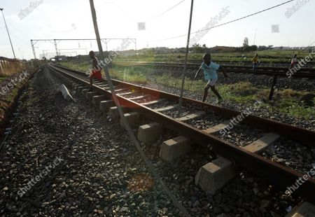 Children cross a vandalised railway line in Soweto, South Africa, . South African President Cyril Ramaphosa announced in parliament that his government will be extending relief measures to the country's poor who have been hurt by the economic downturn caused by COVID-19