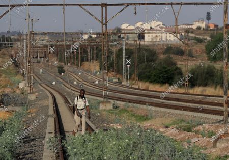 Man walks alongside a vandalised railway line in Soweto, South Africa, . South African President Cyril Ramaphosa announced in parliament that his government will be extending relief measures to the country's poor who have been hurt by the economic downturn caused by COVID-19