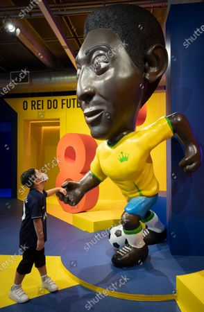 Boy touches the hand of a cartoon-style sculpture of soccer legend Pele at an exhibit marking his 80th birthday at the Soccer Museum in Sao Paulo, Brazil, . The museum reopened on Thursday after a seven-month coronavirus pandemic shutdown to stage a Pele exhibit showing highlights from his long and storied life and career. His actual birthday is Oct. 23