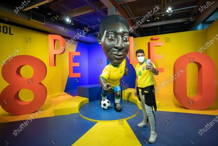 Visitor takes a selfie in front of a cartoon-style sculpture of soccer legend Pele at an exhibit marking his 80th birthday at the Soccer Museum in Sao Paulo, Brazil, . The museum reopened on Thursday after a seven-month coronavirus pandemic shutdown to stage a Pele exhibit showing highlights from his long and storied life and career. His actual birthday is Oct. 23