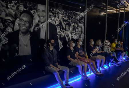 Visitors watch a film about the life of soccer legend Pele at an exhibit marking his 80th birthday at the Soccer Museum in Sao Paulo, Brazil, . The museum reopened on Thursday after a seven-month coronavirus pandemic shutdown to stage a Pele exhibit showing highlights from his long and storied life and career. His actual birthday is Oct. 23
