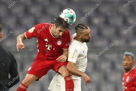Bayern's Javi Martinez, left, jumps for a header with Duren's Baris Sarikaaya during the 1st round German Soccer Cup match between FC Bayern Munich and FC Duren, at the Allianz Arena in Munich, Germany