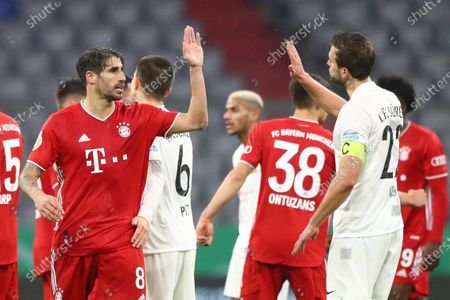 Bayern's Javi Martinez, left, hits a high five with Duren's Mario Weber at the end of the 1st round German Soccer Cup match between FC Bayern Munich and FC Duren, at the Allianz Arena in Munich, Germany
