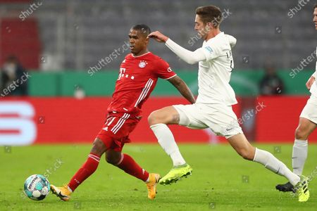 Bayern's Douglas Costa, left, challenges for the ball with Duren's Jannis Becker, right, during the 1st round German Soccer Cup match between FC Bayern Munich and FC Duren, at the Allianz Arena in Munich, Germany
