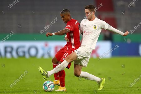 Bayern's Douglas Costa, left, challenges for the ball with Duren's Jannis Becker during the 1st round German Soccer Cup match between FC Bayern Munich and FC Duren, at the Allianz Arena in Munich, Germany
