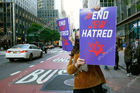 Young woman holds a sign toward oncoming traffic on Third Avenue outside the offices of New York Gov. Andrew Cuomo, in New York. Some members of the Jewish community are angered at Cuomo's recent move ordering schools to close in Orthodox Jewish communities in Brooklyn and north of New York City where coronavirus cases are trending upward. Three Rockland County Jewish congregations filed a lawsuit Wednesday accusing Cuomo of engaging in a streak of anti-Semitic discrimination with a crackdown on religious gatherings