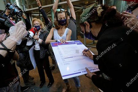 """Woman holds a petition calling for an end to """"Jew Hatred"""" as another woman signs her name to it during a protest outside the offices of New York Gov. Andrew Cuomo, in New York. Three Rockland County Jewish congregations are suing New York state and Gov. Andrew Cuomo, saying he engaged in a """"streak of anti-Semitic discrimination"""" with a recent crackdown on religious gatherings to reduce the state's coronavirus infection rate. The suit was filed in Manhattan federal court on Wednesday"""