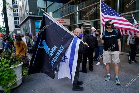 Man holds a Yad Yamin #Fightback flag along with an Israeli flag as he stands next to another man with an American flag as they joined protesters outside the offices of New York Gov. Andrew Cuomo, in New York. Three Rockland County Jewish congregations filed a lawsuit Wednesday accusing Gov. Andrew Cuomo of engaging in a streak of anti-Semitic discrimination with a crackdown on religious gatherings. The Manhattan federal court lawsuit says Cuomo has made numerous discriminatory statements about the Jewish Orthodox community