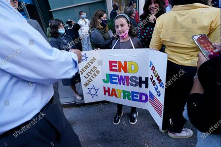"""Young girl holds a poster she made as she prepares to pose for a cell phone photograph for a relative as she and others joined protesters outside the offices of New York Gov. Andrew Cuomo, in New York. Three Rockland County Jewish congregations are suing New York state and Cuomo, saying he engaged in a """"streak of anti-Semitic discrimination"""" with a recent crackdown on religious gatherings to reduce the state's coronavirus infection rate"""