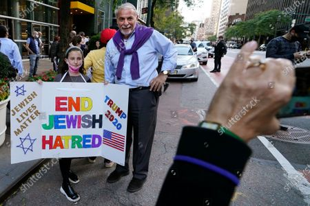 """Young girl poses for a cell phone photo with a homemade sign as she joined protesters outside the offices of New York Gov. Andrew Cuomo, in New York. Three Rockland County Jewish congregations are suing New York state and Gov. Andrew Cuomo, saying he engaged in a """"streak of anti-Semitic discrimination"""" with a recent crackdown on religious gatherings to reduce the state's coronavirus infection rate"""