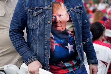 Erik Camara wears a T-shirt of President Donald Trump as he arrives for a campaign rally featuring Vice President Mike Pence at the Cuban Memorial Monument, in Miami