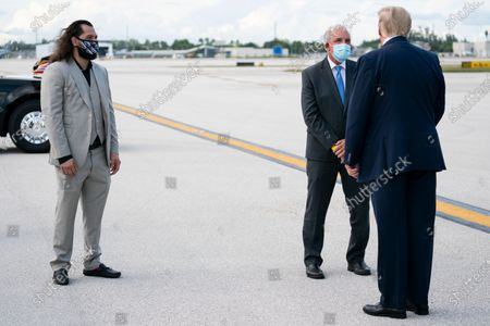 President Donald Trump is greeted by UFC fighter Jorge Masvidal, left, and Miami-Dade County Mayor Carlos Gimenez after arriving at Miami International Airport, in Miami
