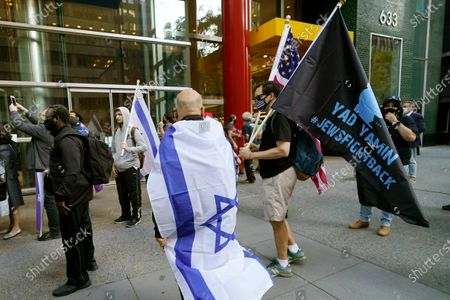 Protesters gather on the sidewalk outside the offices of New York Gov. Andrew Cuomo, in New York. Three Rockland County Jewish congregations filed a lawsuit Wednesday accusing Cuomo of engaging in a streak of anti-Semitic discrimination with a crackdown on religious gatherings