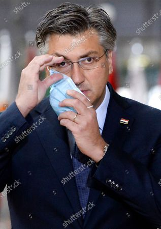 Croatia's Prime Minister Andrej Plenkovic takes off his protective face mask as he arrives for an EU summit in Brussels, . European Union leaders meet for the second day of an EU summit, amid the worsening coronavirus pandemic, to discuss topics on foreign policy issues