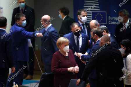 German Chancellor Angela Merkel, center, speaks with Bulgaria's Prime Minister Boyko Borissov during a round table meeting at an EU summit in Brussels, . European Union leaders meet for the second day of an EU summit, amid the worsening coronavirus pandemic, to discuss topics on foreign policy issues