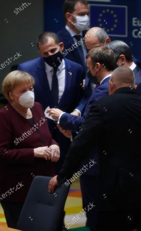 German Chancellor Angela Merkel, left, speaks with Bulgaria's Prime Minister Boyko Borissov during a round table meeting at an EU summit in Brussels, . European Union leaders meet for the second day of an EU summit, amid the worsening coronavirus pandemic, to discuss topics on foreign policy issues