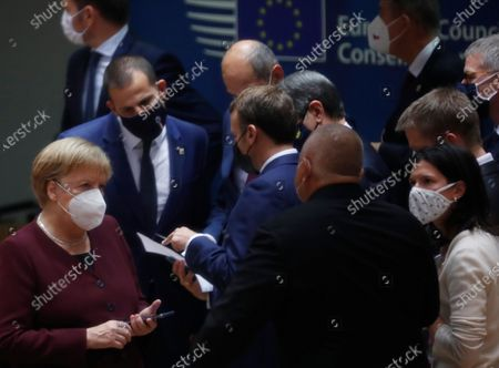 German Chancellor Angela Merkel, left, speaks with French President Emmanuel Macron, center left, and Bulgaria's Prime Minister Boyko Borissov, center right, during a round table meeting at an EU summit in Brussels, . European Union leaders meet for the second day of an EU summit, amid the worsening coronavirus pandemic, to discuss topics on foreign policy issues