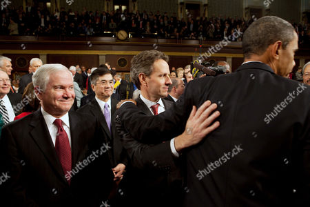 United States Secretary of the Treasury Timothy F. Geithner patting U.S. President Barack Obama on the back as he leaves the House Chamber at the conclusion of his State of the Union address. At left is U.S. Secretary of Defence Robert M. Gates