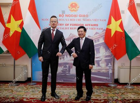 Hungarian Foreign Minister Peter Szijjarto and Vietnamese Foreign Minister Pham Binh Minh elbow as they greet each other in Hanoi, Vietnam, on . Szijjarto is on a visit to the Asian country to reconnect bilateral cooperation disrupted by COVID-19