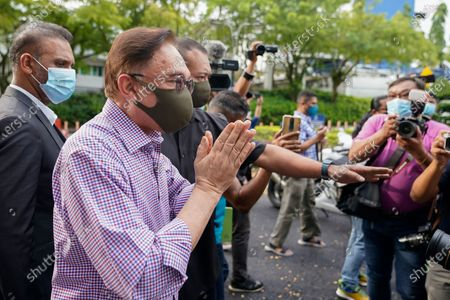 Malaysian opposition leader Anwar Ibrahim gestures after speaking to media outside police headquarters in Kuala Lumpur, Malaysia, . Anwar was questioned by police over the dissemination of a purported list of lawmakers supporting his bid to oust the government