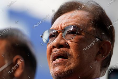Malaysian opposition leader Anwar Ibrahim speaks to media after leaving the police headquarters in Kuala Lumpur, Malaysia, . Anwar was questioned by police over the dissemination of a purported list of lawmakers supporting his bid to oust the government
