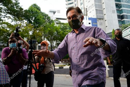 Malaysian opposition leader Anwar Ibrahim walks to media after leaving the police headquarters in Kuala Lumpur, Malaysia, . Anwar was questioned by police over the dissemination of a purported list of lawmakers supporting his bid to oust the government