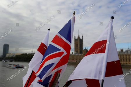 """English flags and a Union flag fly above a souvenir stand opposite Britain's Parliament in London, . Britain's foreign minister says there are only narrow differences remaining in trade talks between the U.K. and the European Union. But Dominic Raab insists the bloc must show more """"flexibility"""" if it wants to make a deal"""