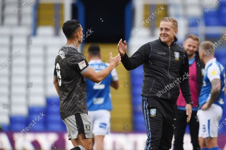 Garry Monk manager of Sheffield Wednesday high fives Joey Pelupessy of Sheffield Wednesday.