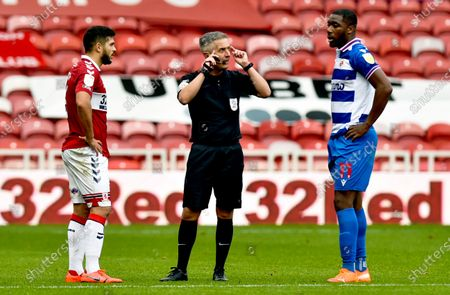 Referee Darren Bond shows lectures Yakou Meite of Reading and Sam Morsy of Middlesbrough