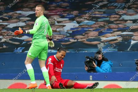 Virgil van Dijk of Liverpool lies on the pitch following a collision with Everton goalkeeper Jordan Pickford