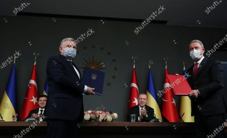 Turkish President Recep Tayyip Erdogan, rear right, and Ukrainian President Volodymyr Zelenskiy, rear left, applaud as Turkey's Defense Minister Hulusi Akar, right, and Ukraine's Defense Minister Andrii Taran show the agreement they have signed, in Istanbul, . Turkey and Ukraine signed military cooperation agreements on Friday, deepening their defense partnership seen as an effort to counterbalance Russia's dominance in the Black Sea region