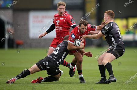 Stock Photo of Paul Asquith of Scarlets is tackled by Joe Thomas and Aneurin Owen of Dragons.